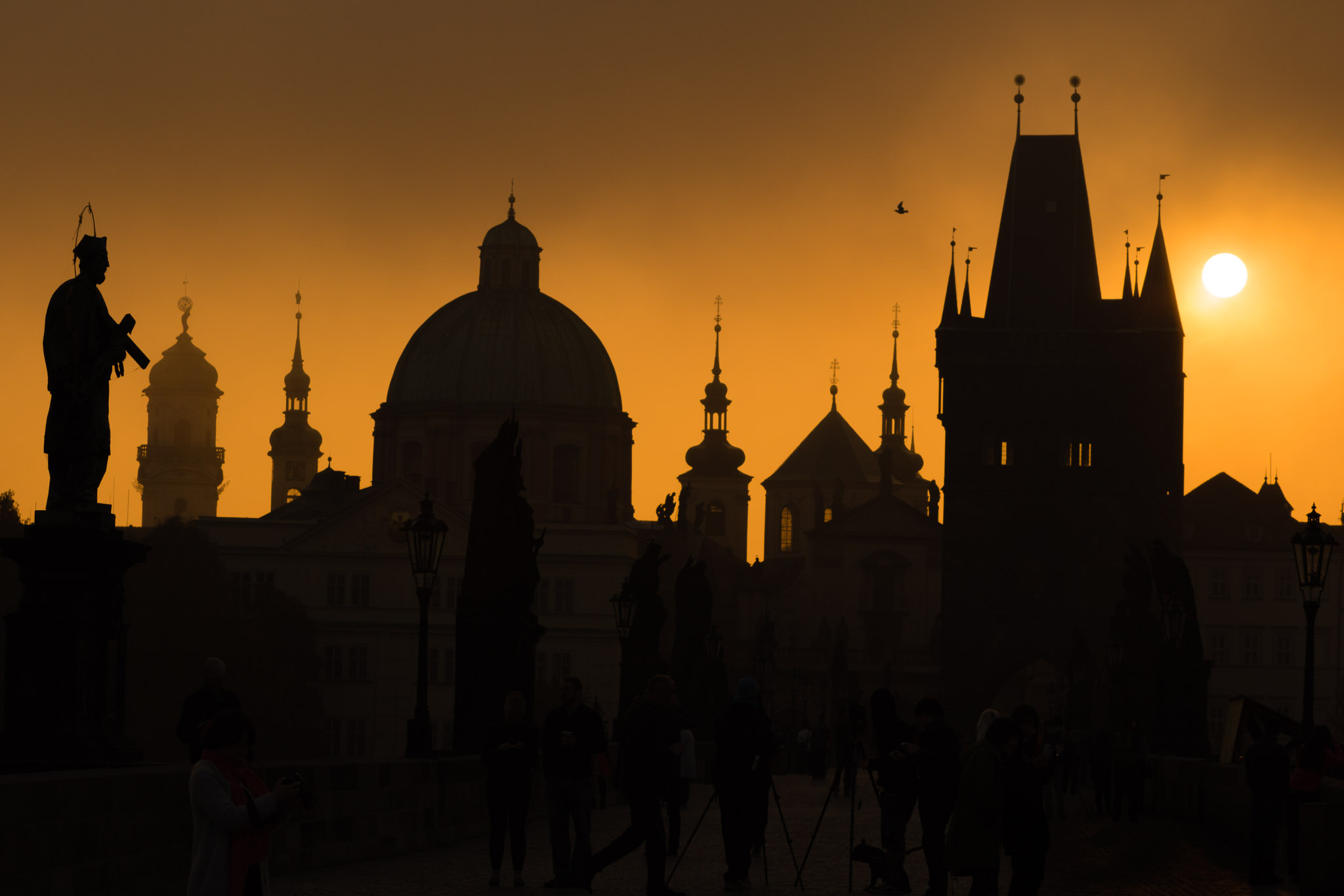 Silhouettes of Prague towers and statues on Charles bridge during sunrise